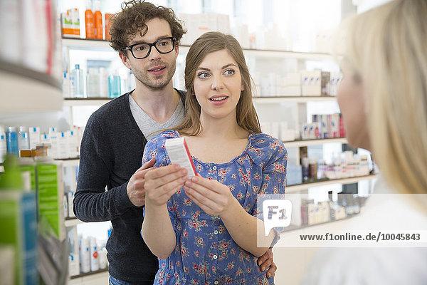 Female pharmacist advising customers