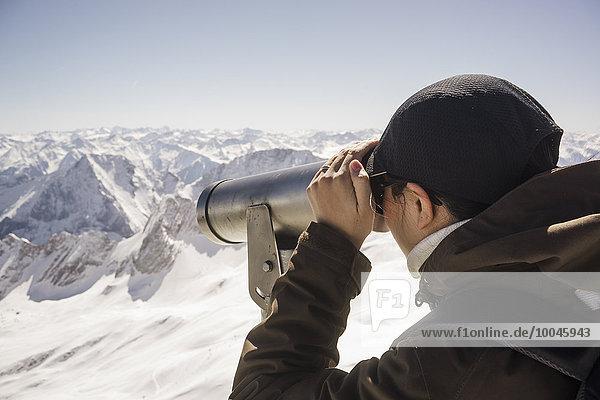 Deutschland  Bayern  Frau schaut durchs Teleskop auf die Zugspitze