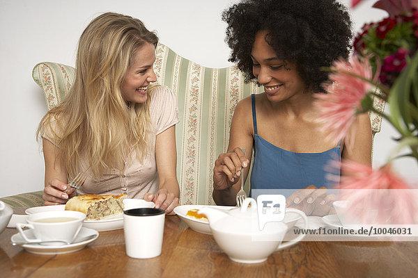 Zwei Freundinnen essen Kuchen und trinken Tee in einem Café.