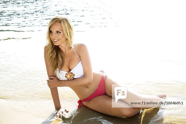 Lächelnde blonde Frau im Bikini am Strand vor dem Wasser sitzend