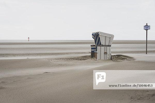 Deutschland  Schleswig-Holstein  St. Peter-Ording  Strandstuhl mit Kapuze bei stürmischem Wetter