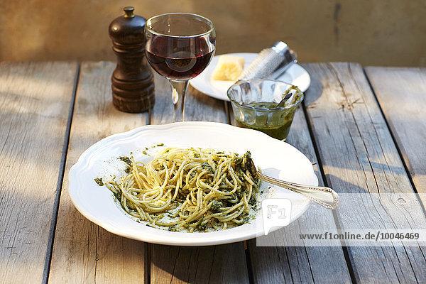 Spaghetti mit Basilikumpesto und einem Glas Rotwein
