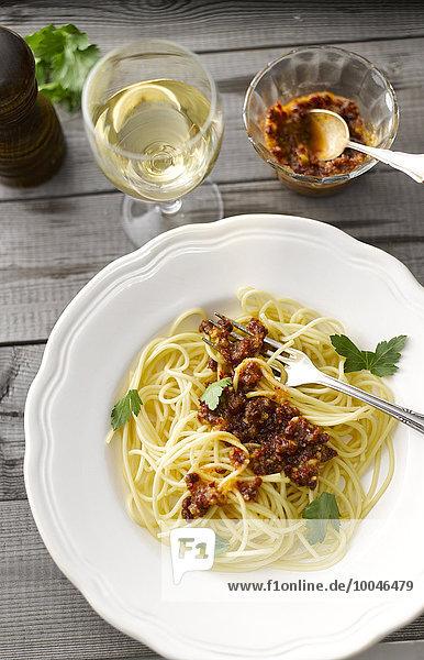 Spaghetti mit Tomatenpesto und einem Glas Weißwein