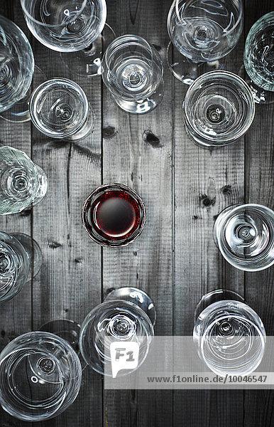 Glas Rotwein und leere Weingläser auf Holz