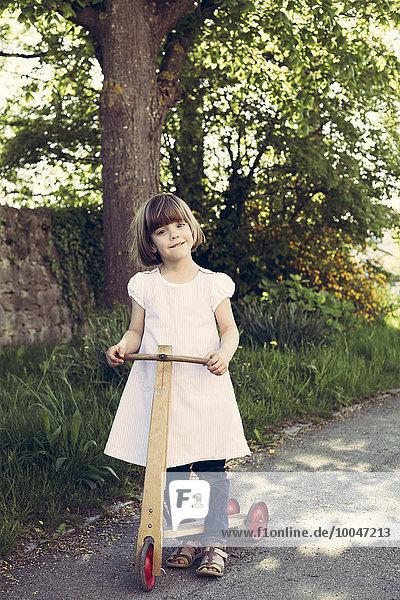 Porträt des kleinen Mädchens mit altem Holzroller