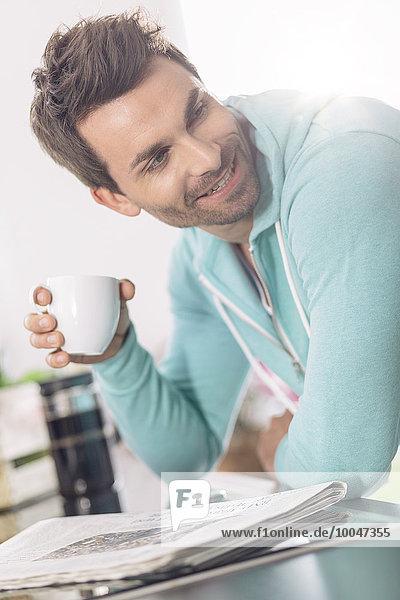 Porträt des Mannes mit Tasse Kaffee und Zeitung in der Küche