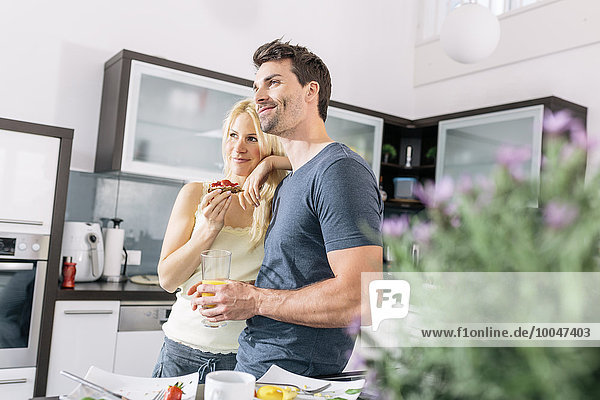 Couple having breakfast in the kitchen at weekend