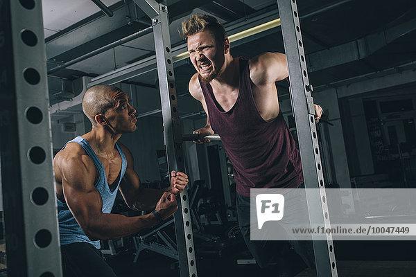 Zwei Freunde trainieren Dips am Power Rack im Fitnessstudio