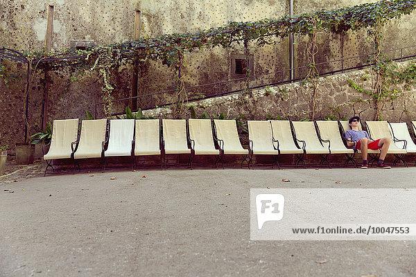 Spanien  Mallorca  Junge entspannt in einem Liegestuhl  Stuhlreihe Spanien, Mallorca, Junge entspannt in einem Liegestuhl, Stuhlreihe