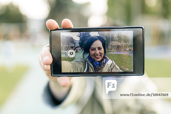 Reife Frau nimmt Selfie  hält ein Smartphone.