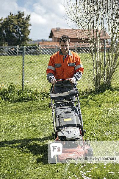 Spanien  junger Mann beim Rasenmähen