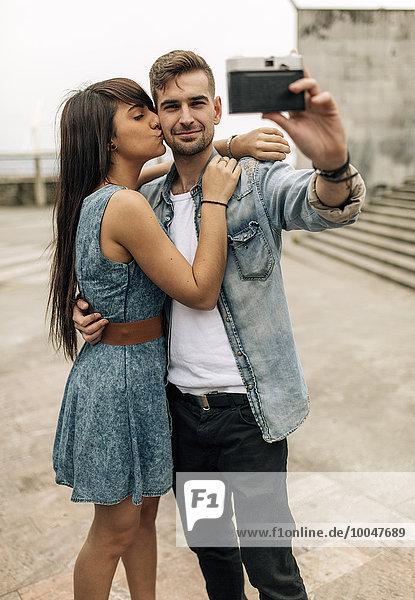 Spanien  Gijon  junges Paar  das einen Selfie mit einer alten Kamera nimmt