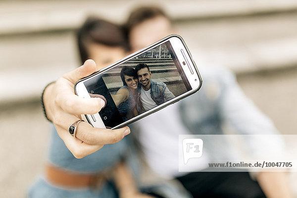 Spanien  Gijon  junges verliebtes Paar mit Smartphone