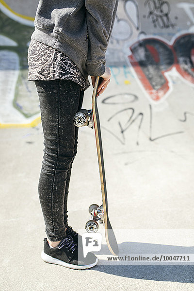 Spanien  Gijon  Skateboarderin auf Skateboard lehnend