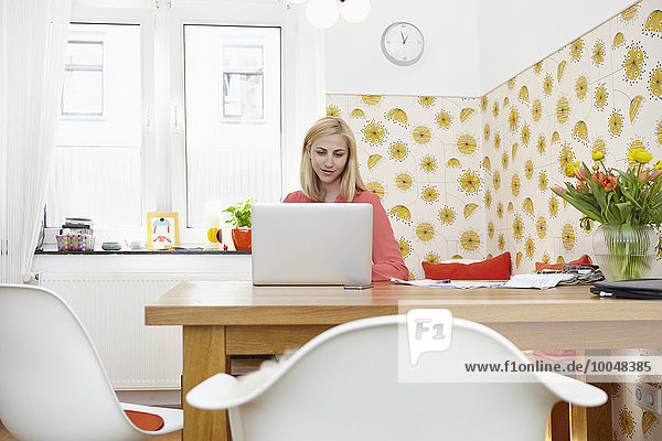 Young woman using laptop at her home office