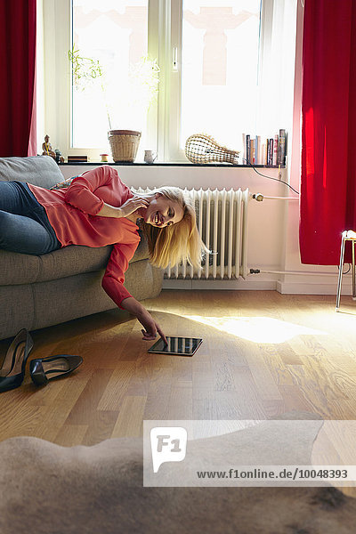 Young woman with digital tablet lying on couch at home