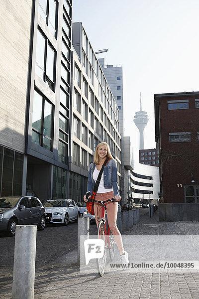 Deutschland  Düsseldorf  glückliche blonde Frau mit Fahrrad