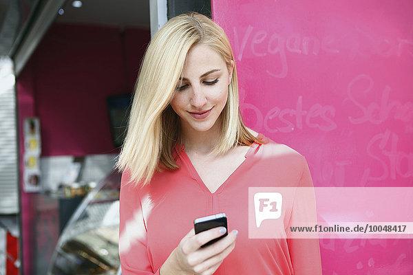 Lächelnde  blonde Frau schaut auf ihr Smartphone vor einem Marktstand.