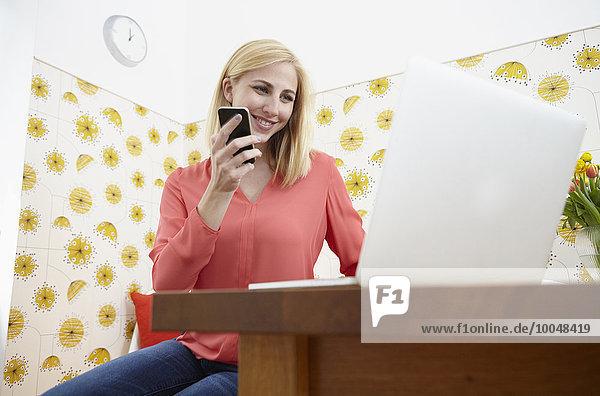 Lächelnde junge Frau mit Smartphone und Laptop im Home Office