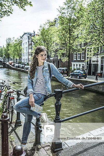 Niederlande  Amsterdam  Touristinnen mit Stadtplan vor dem Stadtkanal