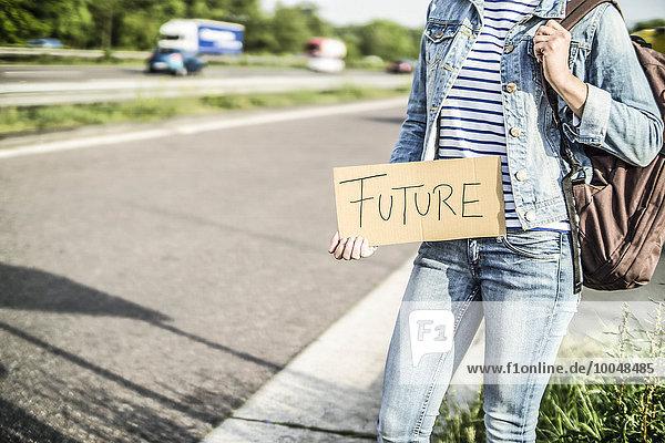 Deutschland  Tramperin mit dem Schild Zukunft am Straßenrand