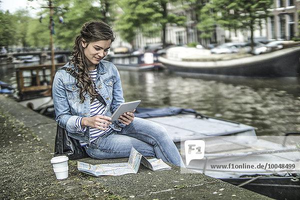 Niederlande  Amsterdam  Touristin mit digitalem Tablett vor dem Stadtkanal