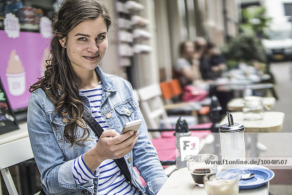 Netherlands  Amsterdam  portrait of female tourist sitting in a street cafe