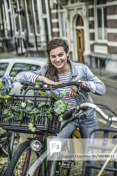 Netherlands  Amsterdam  smiling woman leaning on her bicycle