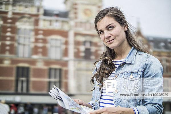 Niederlande  Amsterdam  Frau mit Stadtplan vor dem Hauptbahnhof
