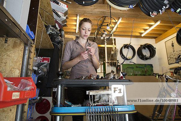 Junge Frau  die in einer Fahrradwerkstatt arbeitet