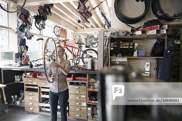 Junge Frau in einer Werkstatt mit Fahrradrad