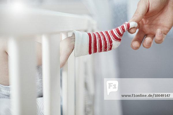 Vater zieht Babysocke in der Krippe aus