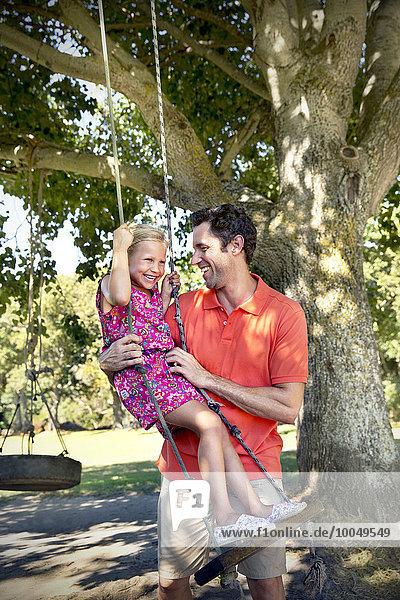 Vater spielt mit Tochter beim Schaukeln