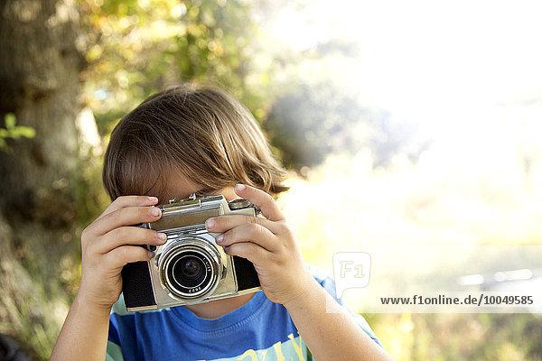 Junge mit analoger Kamera beim Fotografieren im Freien