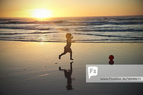 Junge rennt am Strand bei Sonnenuntergang