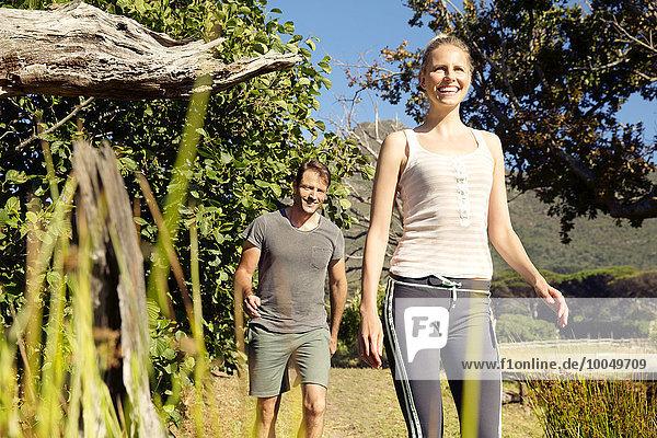 Lächelndes Paar beim Spaziergang durch die ländliche Landschaft