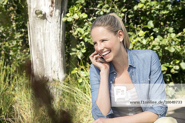 Glückliche Frau am Handy in ländlicher Landschaft