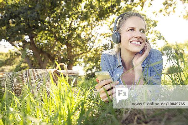 Lächelnde Frau liegt auf der Wiese und hört Musik vom Smartphone.