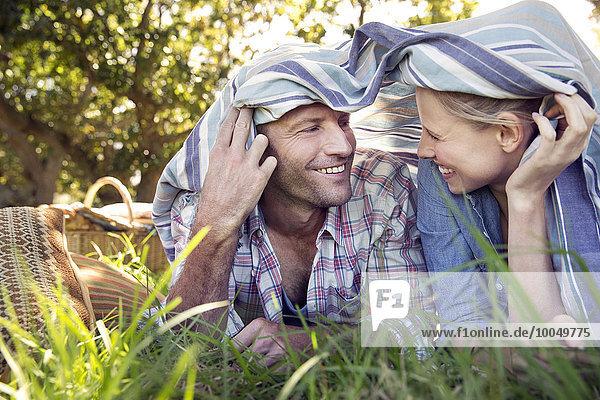 Happy couple lying on meadow under a blanket