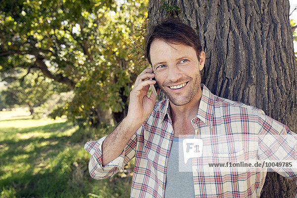 Smiling man on cell phone at tree