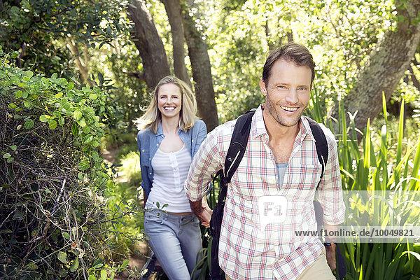 Lächelndes Paar wandert Hand in Hand im Wald