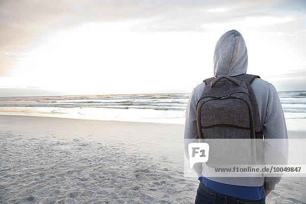 Junger Mann mit Rucksack am Strand bei Sonnenaufgang