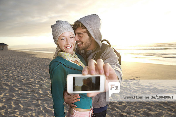 Junges Paar bei Sonnenaufgang mit einem Selfie am Strand