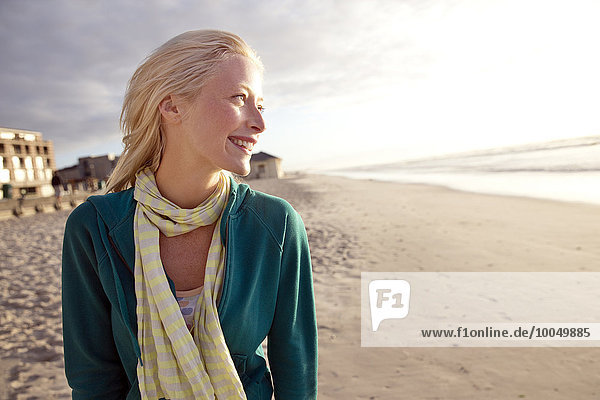 Lächelnde junge Frau am Strand bei Sonnenaufgang