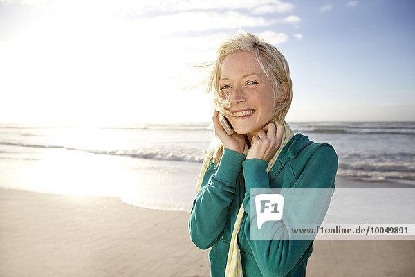 Lächelnde junge Frau am Strand bei Sonnenaufgang per Handy