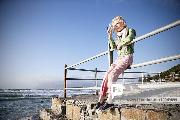 Junge Frau an der Küste beim Fotografieren