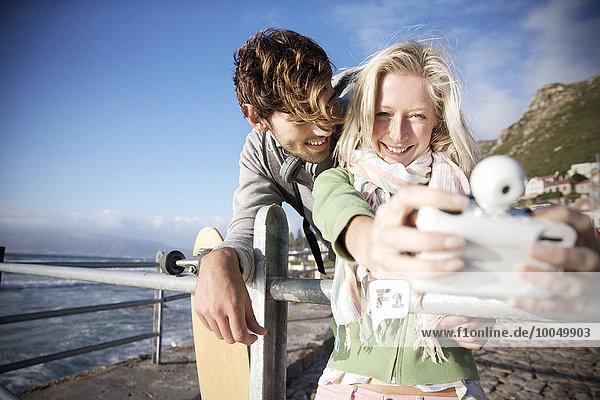 Ein glückliches junges Paar  das einen Selfie an der Küste nimmt.