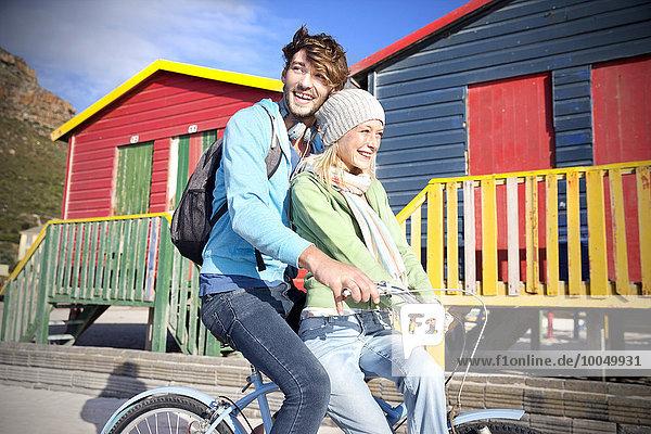 Junges Paar beim Radfahren auf bunten Strandhütten