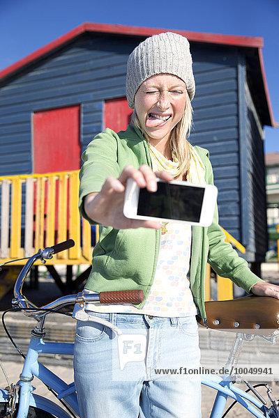Verspielte junge Frau nimmt Selfie mit dem Fahrrad vor der bunten Strandhütte