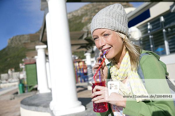 Junge Frau im Freien trinkt Erfrischungsgetränk